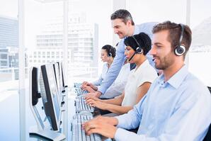 Side view of manager and executives with headsets using computers in the office